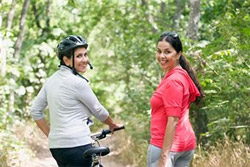 Women outside walking and biking